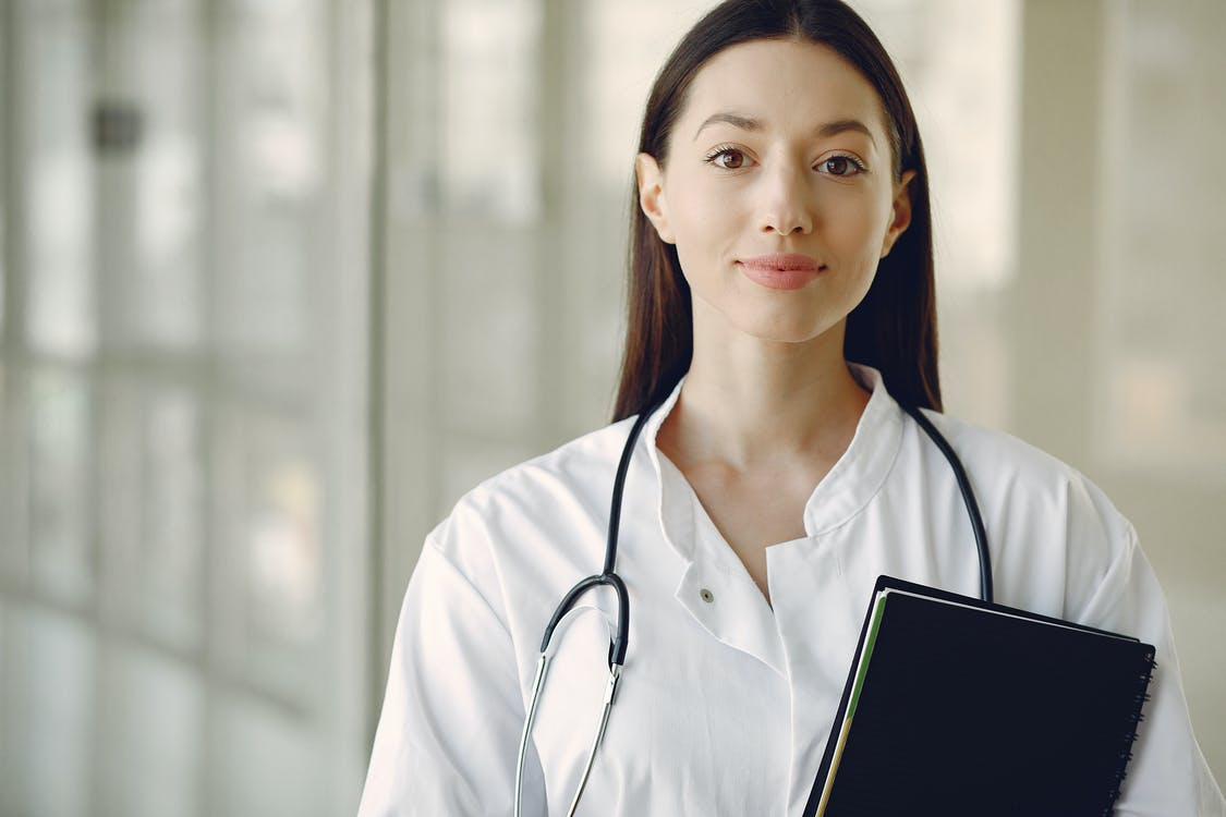 Young doctor in uniform with stethoscope and notebook in medical room