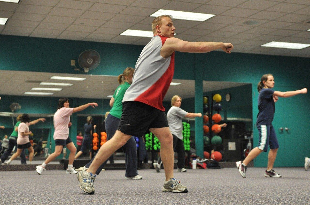 A group of people exercising in a gym Description automatically generated with medium confidence